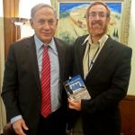 Yehuda Glick holds a copy of his guide to ascending the Temple Mount with Prime Minister Benjamin Netanyahu