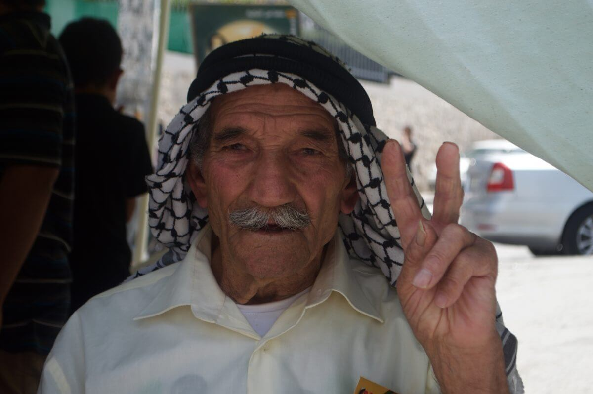 One man, a 90-year-old from Aida refugee camp, didn't participate in the march, but waited in the summer heat under a tent for the march to meet him at the city-center. (Photo by Sheren Khalel)