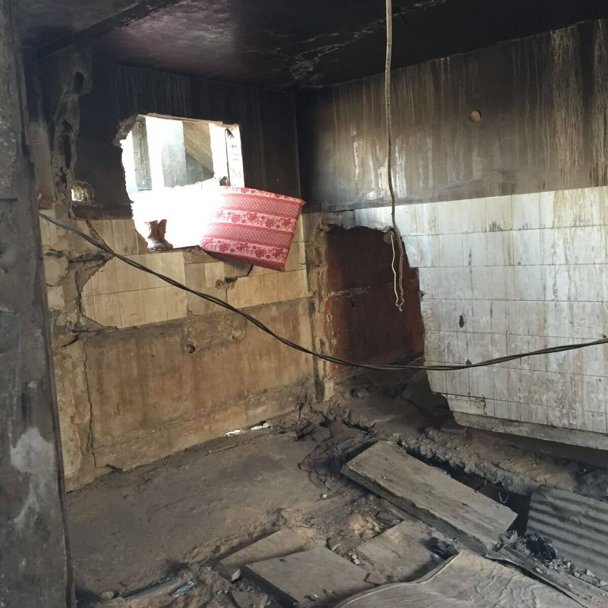 A room in a partially destroyed house in Shuja'yya where seven people live (photo Nancy Murray, April 19)
