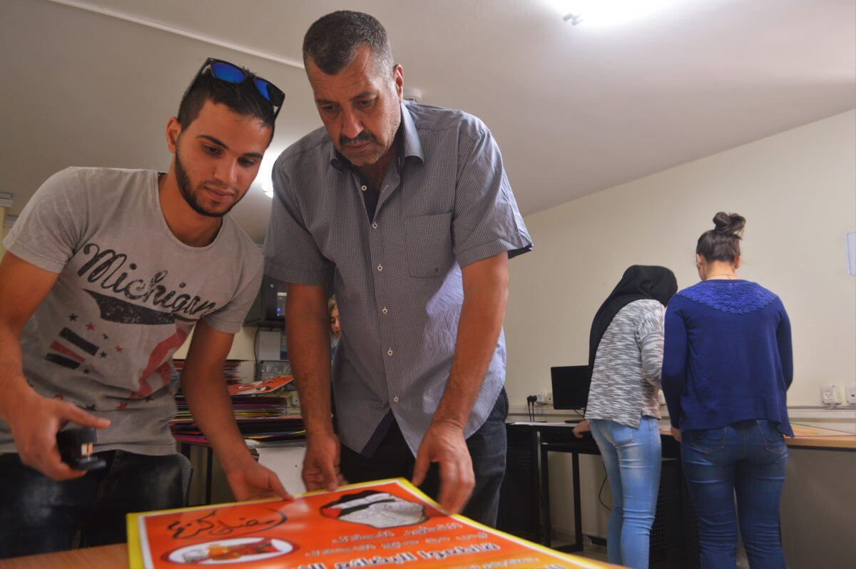 Mazin al-Azzeh helps youth put together stacks of BDS campaign posters. (Photo: Sheren Khalel/Mondoweiss)