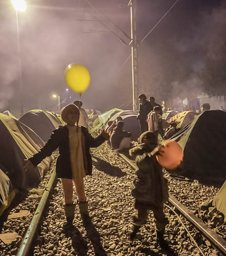 Children play with balloons on the train tracks in the Idomeni refugee camp in Greece. The air is full of smoke as the refugees do their best to stay warm. (Photo: Hala Gabriel)
