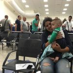 """Marina Hansen: """"My friend and I amuse ourselves while waiting to be interrogated by playing with the babies of Palestinian families who were also waiting to be questioned. Behind her is the line to cross Israeli passport control from Jordan into Israel where we were both rejected and told to sit in the waiting area."""""""