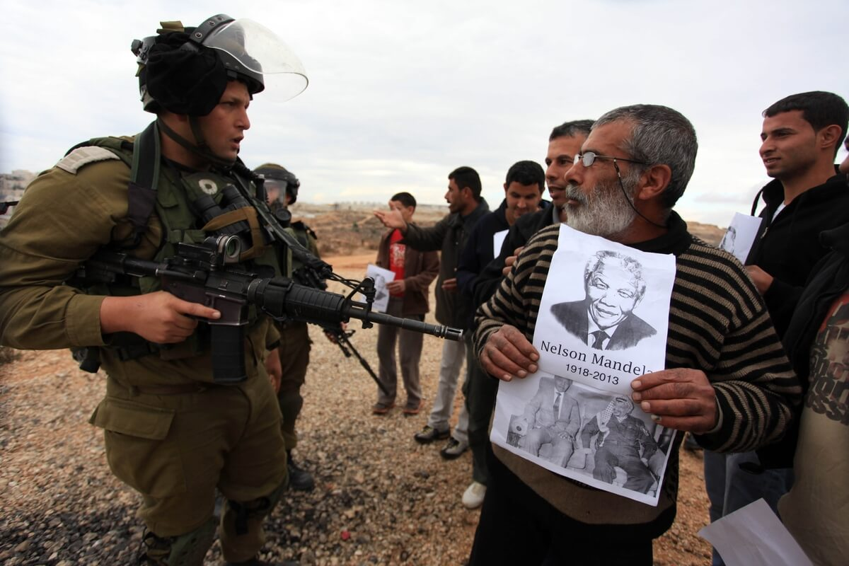 A Palestinian man holds a portrait of late South African president Nelson Mandela as he stands in front of Israeli soldiers during clashes between youths and the army following a weekly protest against Israeli occupation in the West Bank village of Bilin on December 6, 2013. (Photo: Issam Rimawi/APA Images)