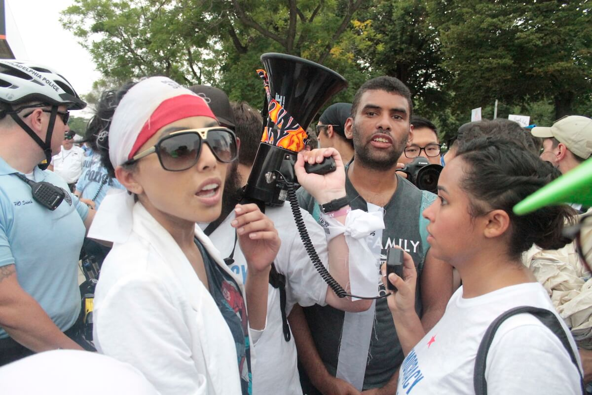 Sameera Khan, 25, a Muslim American and former Ms. New Jersey, holds a megaphone in Philadelphia outside the Democratic National Convention, shouting 'One person, one vote!' and decrying the influence of money in politics. (Photo: Wilson Dizard)