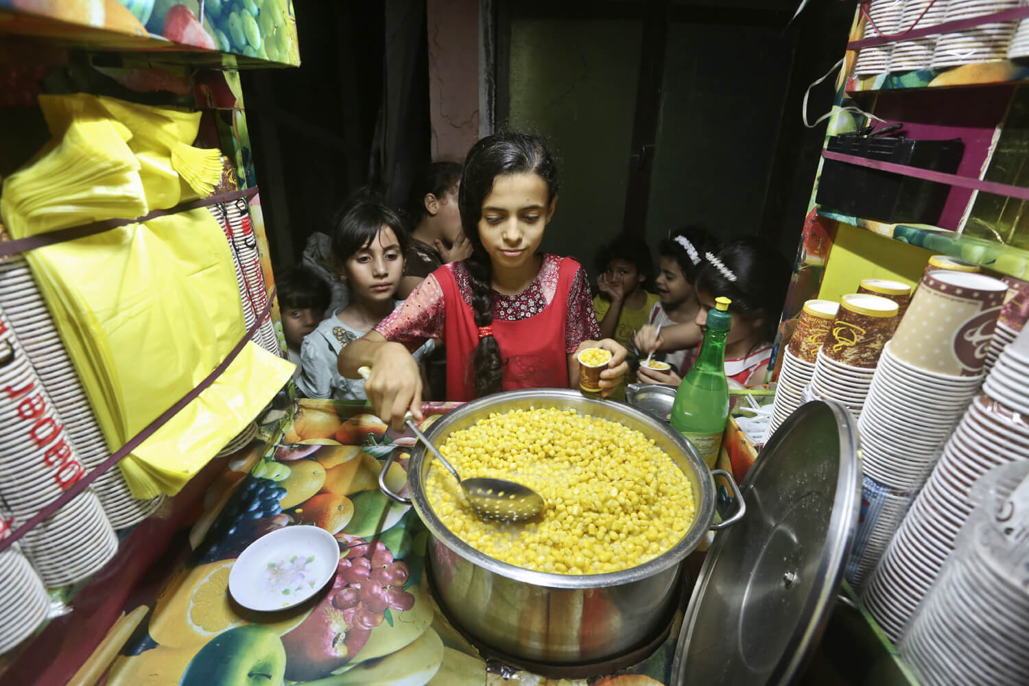 Mervit Baker, 12, sells cups of buttered corn in front of her house in the Al- Zaytoon area, Gaza, June 27, 2016. (Photo: Mohammed Asad)