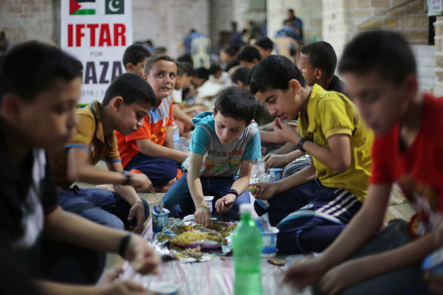 Ahmad Matter, 8, eats breakfast provided by a charitable foundation, at the Great Omari Mosque, Gaza. June 20, 2016. (Photo: Mohammed Asad)