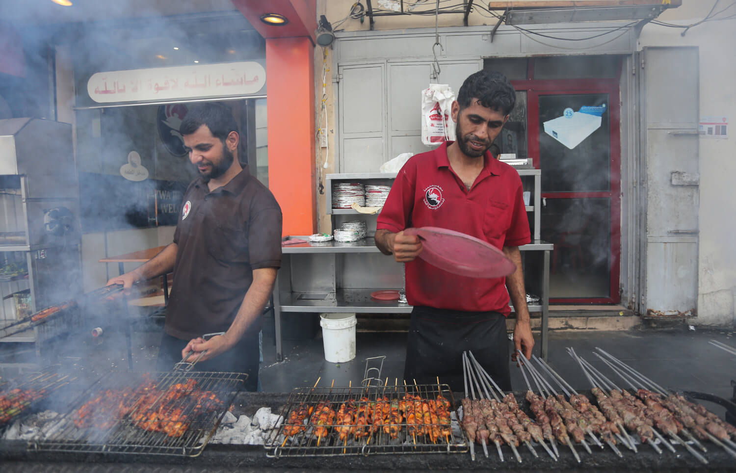 "Al-Qasas brothers barbecue in preparation of the iftar meal at a ""mashawi"" restaurant in Gaza, June 25, 2016. (Photo: Mohammed Asad)"
