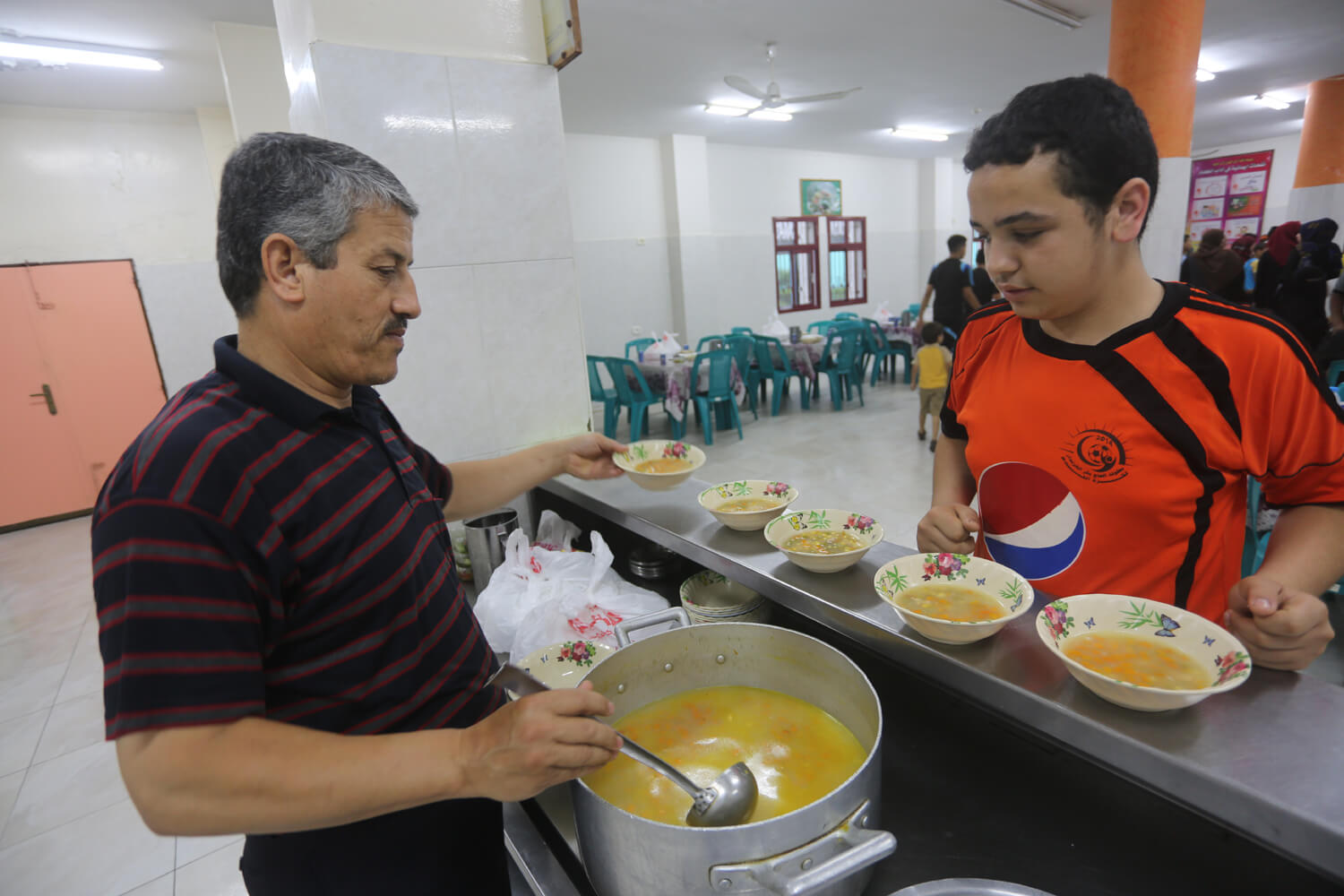 Ahmad Harb, 13, receives a meal from the cook at the Al-Amal Institute for Orphans, June 26, 2016. (Photo: Mohammed Asad)