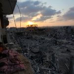 A Palestinian man lies down among a destroyed house after returning home in the Tufah neighborhood in eastern Gaza City on August 31, 2014. (Photo: Ashraf Amra/ APA Images)