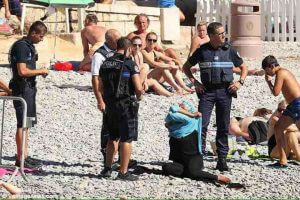 One of several viral photos showing a woman removing her tunic while surrounded by police on a beach in Nice. (Photo: ABDUL AZIM/TWITTER)