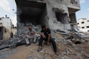 Palestinian men sit amidst the debris of a neighbouring house which police said was damaged after an Israeli air strike destroyed Tayseer Al-Batsh's family house, in Gaza City July 13, 2014. (Photo: Ashraf Amra/APA Images)