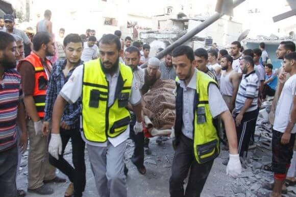 Emergency responders aid Palestinians injured in an Israeli air strike on an UNRWA school in Gaza's Rafah city, on August 3, 2014. The United Nations said 15 were killed in the blast and a further 25 were injured. (Photo: Palestinian Ministry of Health)