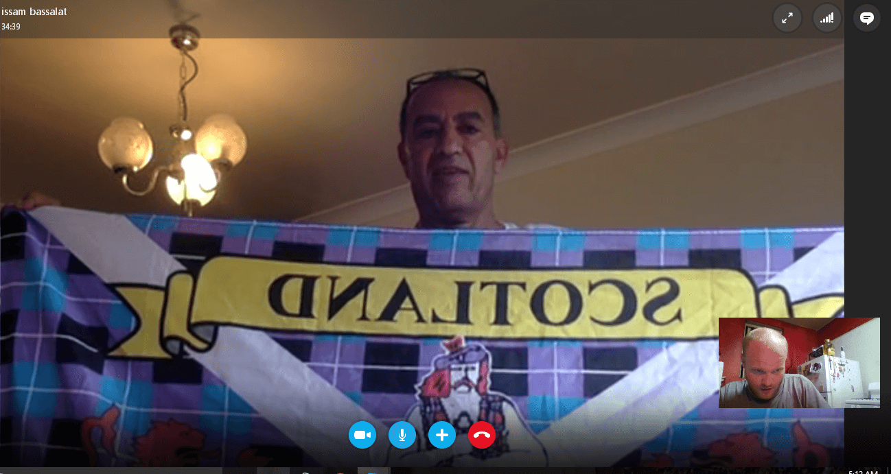 Dr. Issam Hijjawi of Palestine Alliance holds up a Scottish banner during a Skype interview with Mondoweiss.