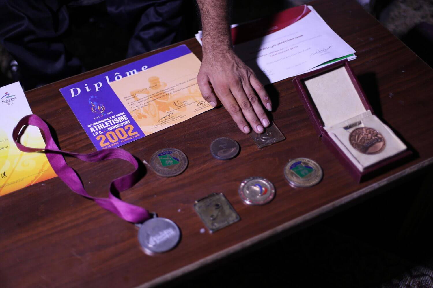 Hossam Azzum displays his medal won in past shot put competitions. Many of his awards were destroyed in 2014 during an Israeli airstrike on his house. (Photo: Mohammed Asad)