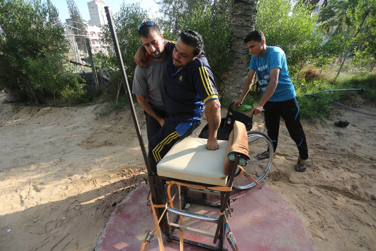 Trainer Mohammed Dahman helps Hossam Azzum into his shot put performance chair. (Photo: Mohammed Asad)
