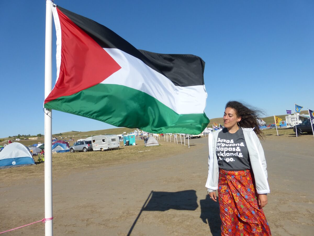 The author standing by the Palestinian flag in Oceti Sakowin Camp