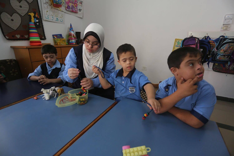 Hiba Shurafa shows students at the Right to Life Society school in Gaza how to make handicrafts (Photo: Mohammed Asad)