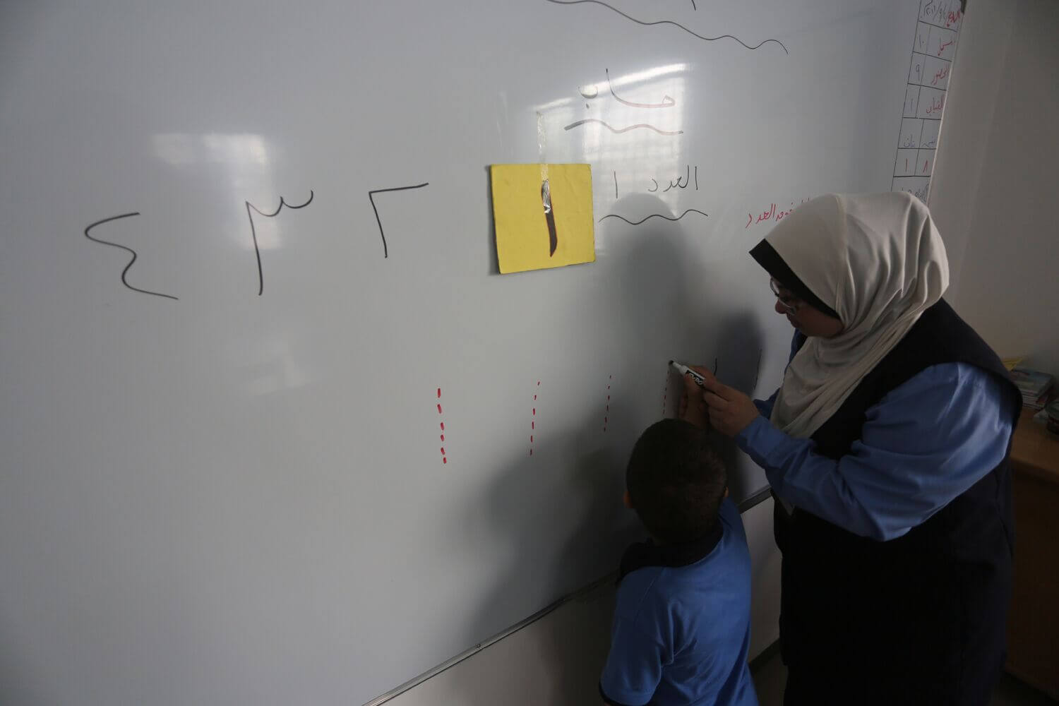 Hiba Shurafa guides a student drawing numbers on the classroom wipe board at the Right to Life Society school for mentally disabled students in the Gaza strip. (Photo: Mohammed Asad)