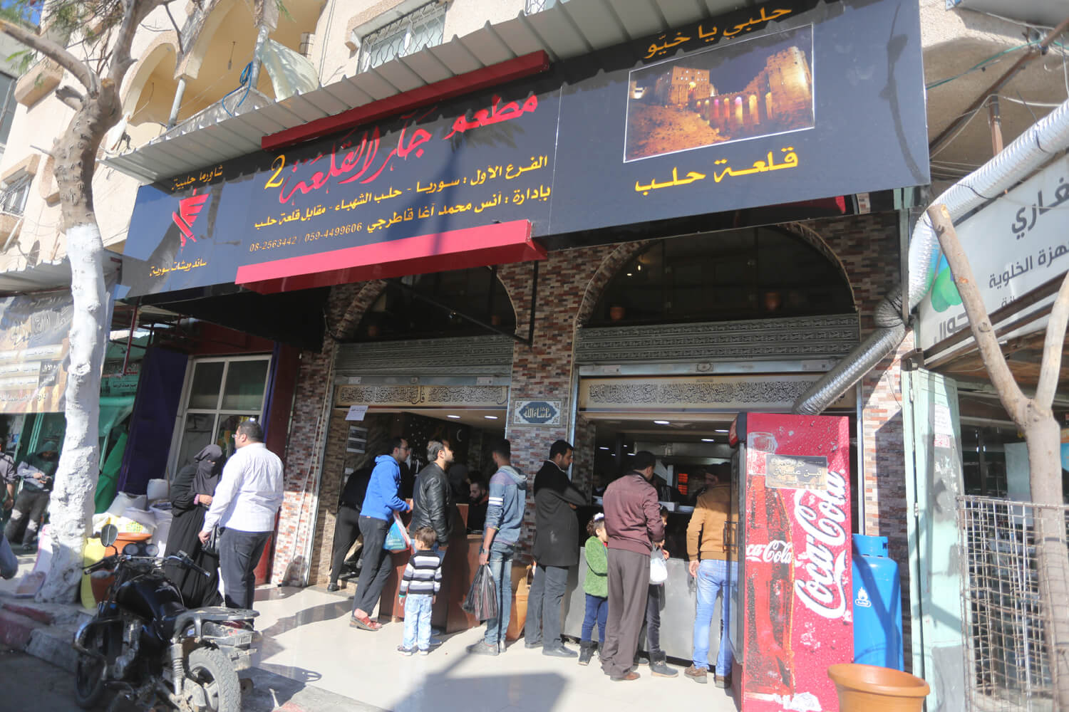 The front of the Syrian Jar Al Qala'a restaurant with a photo of the original location in Aleppo. (Photo: Mohammed Asad)