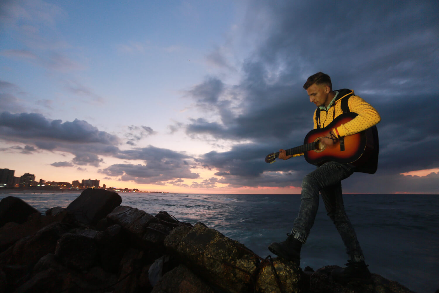 A young man plays the guitar in front of the sea (Photo: Mohammed Asad)