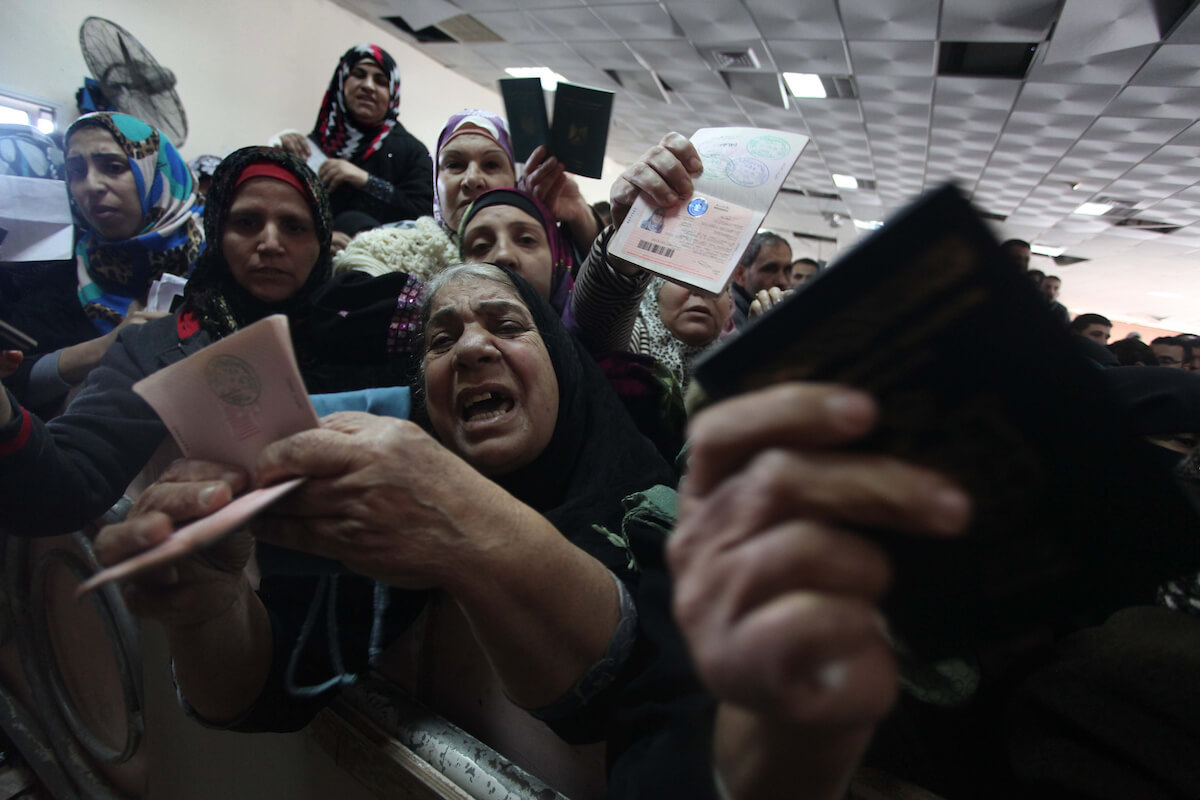 Palestinian women present their passports as they ask for permits to cross into Egypt at the Rafah border crossing between Egypt and the southern Gaza Strip December 23, 2014. (Photo: APA Images/Ashraf Amra)