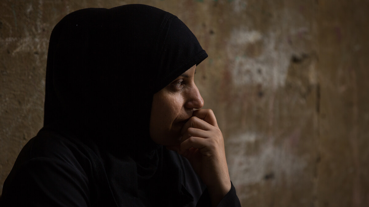 """Bourj el Barajneh Camp, Beirut, Lebanon - 15/10/2016: 33 year old Darjeh Ahed Mousa is from Zooum. """"Yes, I`m from Zooum, but I don't know from where exactly there, I was born in Lebanon. Palestine is a beautiful country, its people, its houses, its trees , everything is beautiful there, I've even seen it on the TV, in the news. I wish I could go."""" """"Palestine? The way they dress, this embroidery. What reminds us of our country here is the clothing, the embroidery, the abayas, the flags of Palestine, this all remind us of Palestine."""" (Photo: Celia Peterson)"""