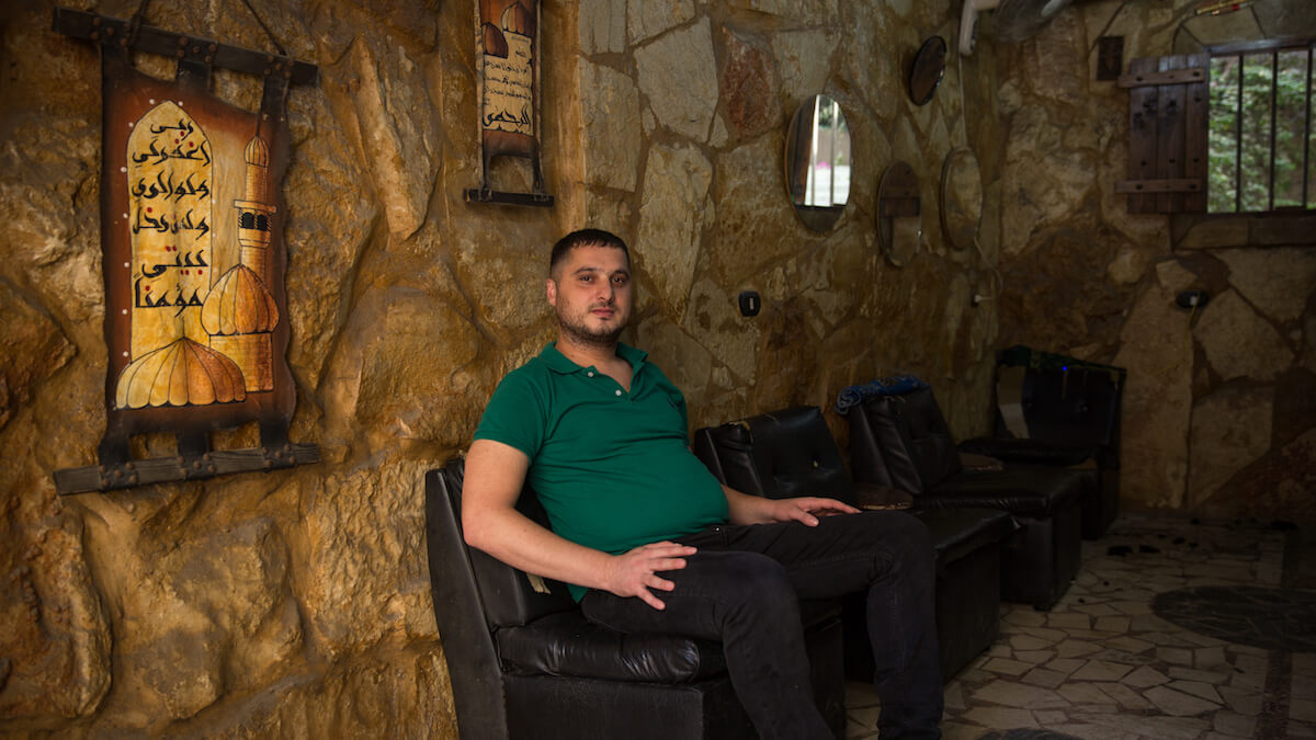 """Bourj el Barajneh Camp, Beirut, Lebanon - 15/10/2016: Ahmad Rafeek al Ali is from Kwaikat, Akka, was born in Lebanon in 1982 and runs a barber's shop in the camp. He has decorated his shop to look like Jerusalem, he found out about Jerusalem's architecture via seeing images on the internet and facebook. """"Our parents, our grandfathers and ancestors used to tell us a lot about Palestine. Our ancestors were farmers and landlords who used to grow olive and lemon trees in villages. They used to tell us about Acre Wall, and how beautiful the city and was, the Wall also was amazing. Our grandfathers used to tell us about that mosque in Acre that had golden columns, originally made of gold, old traditional ones. The mosque is still there till now, all its columns are from gold, covered with gold."""" (Photo: Celia Peterson)"""
