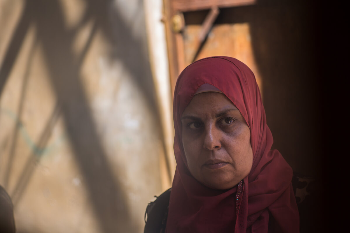 """Bourj el Barajneh Camp, Beirut, Lebanon - 15/10/2016: Heyam Mahmoud, 54 years old, is from the city of Akka, has never lived in Palestine but her mother lived there until she was 9 year's old and passed along some memories of her city: """"Aaka is a beautiful city, the wall is so wide a car can drive on it and it separates the sea from the city. My grandfather used to go to Jazaar mosque and he took my uncle with him to pray. We brought nothing with us, nothing [here] reminds us of Palestine except our memories. We use these memories to apply them in our weddings and social gatherings."""" (Photo: Celia Peterson)"""
