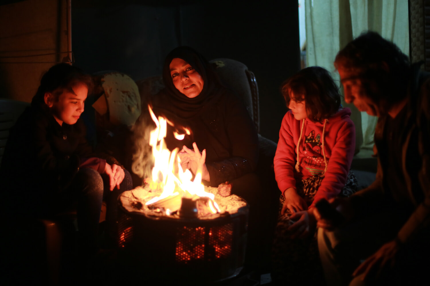 Family warming themselves in the street after their home was destroyed in a Gaza refugee camp (Photo: Mohammed Asad)