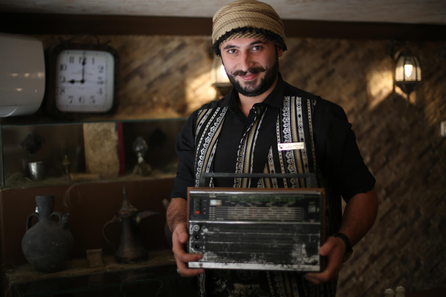 Qatarji with an old radio brought from the Aleppo restaurant. (Photo: Mohammed Asad)