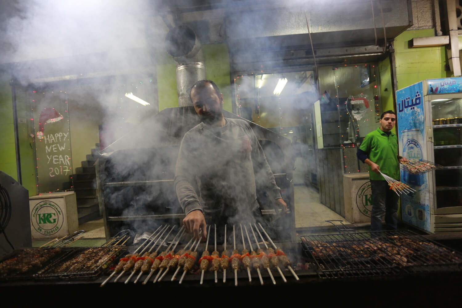 The owner of a restaurant prepares a barbecue for customers (Photo: Mohammed Asad)