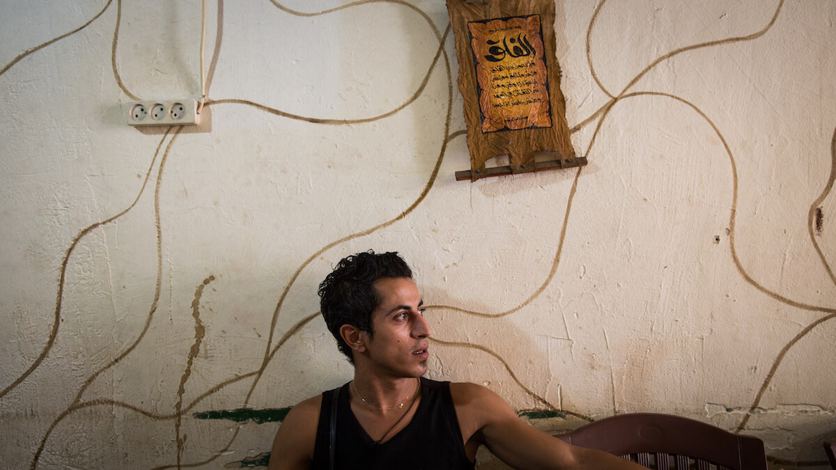"""Bourj el Barajneh Camp, Beirut, Lebanon - 15/10/2016: 26 year old Mohammad is from Safed and works in a coffee shop in the camp. """"And the only that reminds me of Palestine here is the Palestinian accent they speak here in the community. Also when I see an olive tree it reminds me of Palestine. The Palestinian traditions, the clothing, the things they still make, things they still keeping from there. The things that remind me of Palestine are the things I told you about, Palestinian accent they speak here in the community, the Palestinian traditional stories we still tell. Things like the Wheat Mill, things like that I see from the time of our grandfathers. There are even really old people out there who has been born in Palestine, and when sit with them and listen to them talking you feel like you've moved to Palestine itself. Things like these."""" (Photo: Celia Peterson)"""