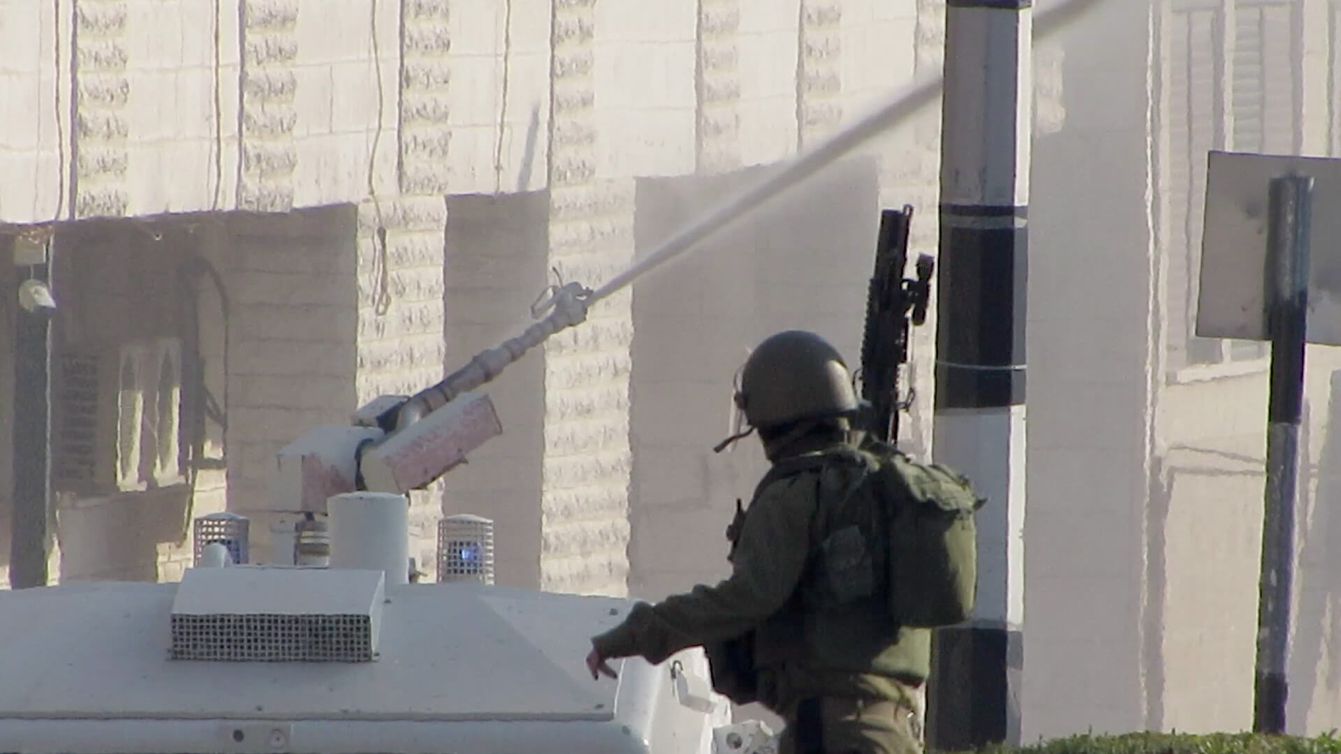 """An Israeli soldier clears out of the way as a specially-built IDF vehicle begins to douse Bethlehem in """"skunk spray"""", chemical warfare intended to make life miserable for the civilian population. Photo: T Suárez"""