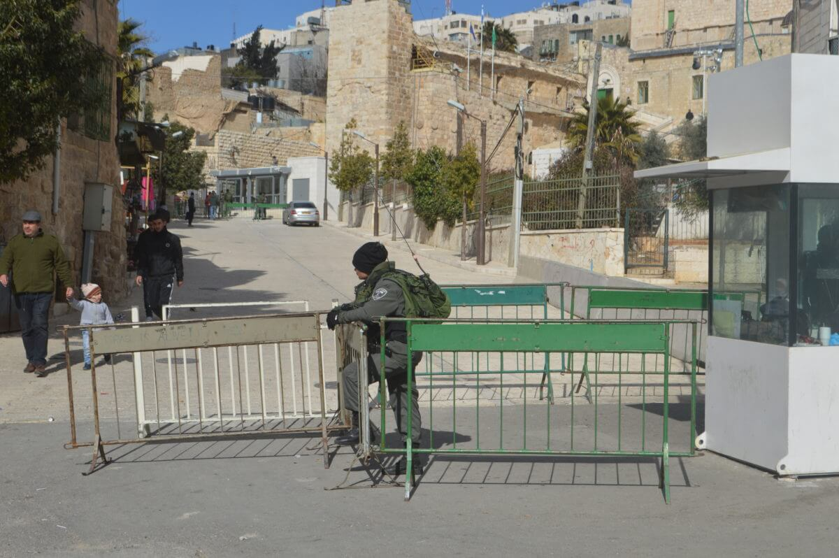 An Israeli soldier guards a checkpoint, a few hundred feet from another checkpoint, in the old city of Hebron, very near to where Elor Azaria shot dead Abed al-Fattah Sharif. (Photo: Sheren Khalel/Mondoweiss)