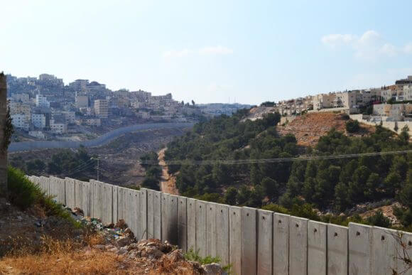 An Israeli settlement sits to the right of Israel's separation wall in East Jerusalem, dividing the Palestinian neighborhood to the left, from other Palestinian neighborhoods in the area. (Photo: Eoghan Rice)