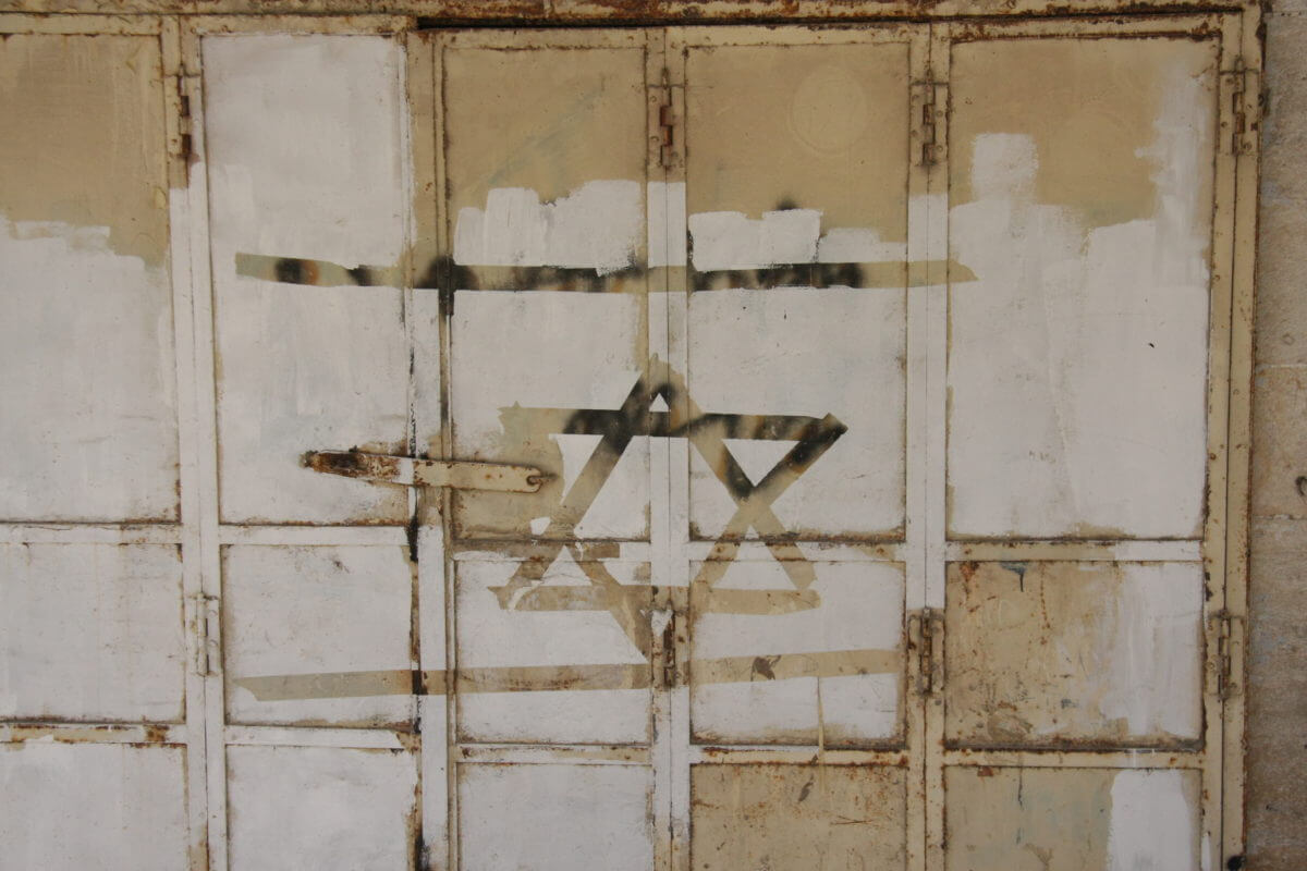 A shuttered Palestinian shop in Hebron closed down by the Israeli military that was vandalized with a Star of David, an ancient Jewish symbol adopted by the Israeli state as a national symbol. (Photo: Lauren Surface)