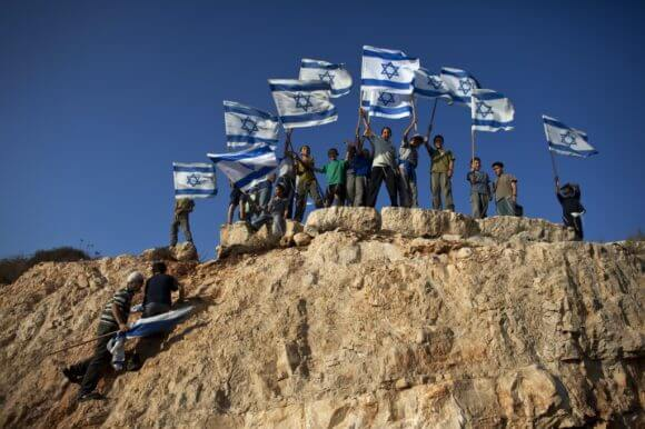 Jewish youth hold Israeli flags at the beginning of a rally march in the West Bank settlement of Itamar, near Nablus September 20, 2011. (Photo: REUTERS/Nir Elias)