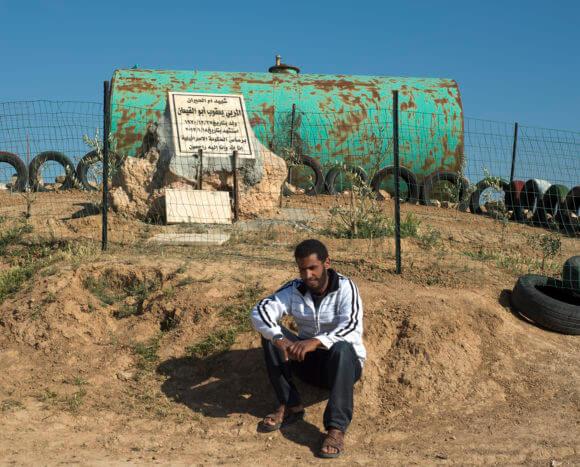 Noor Abu al-Qia'an sits beside a monument dedicated to his father Yakoub Abu al-Qia'an, in Umm al-Hiran. (Photo: Howard Cohen)