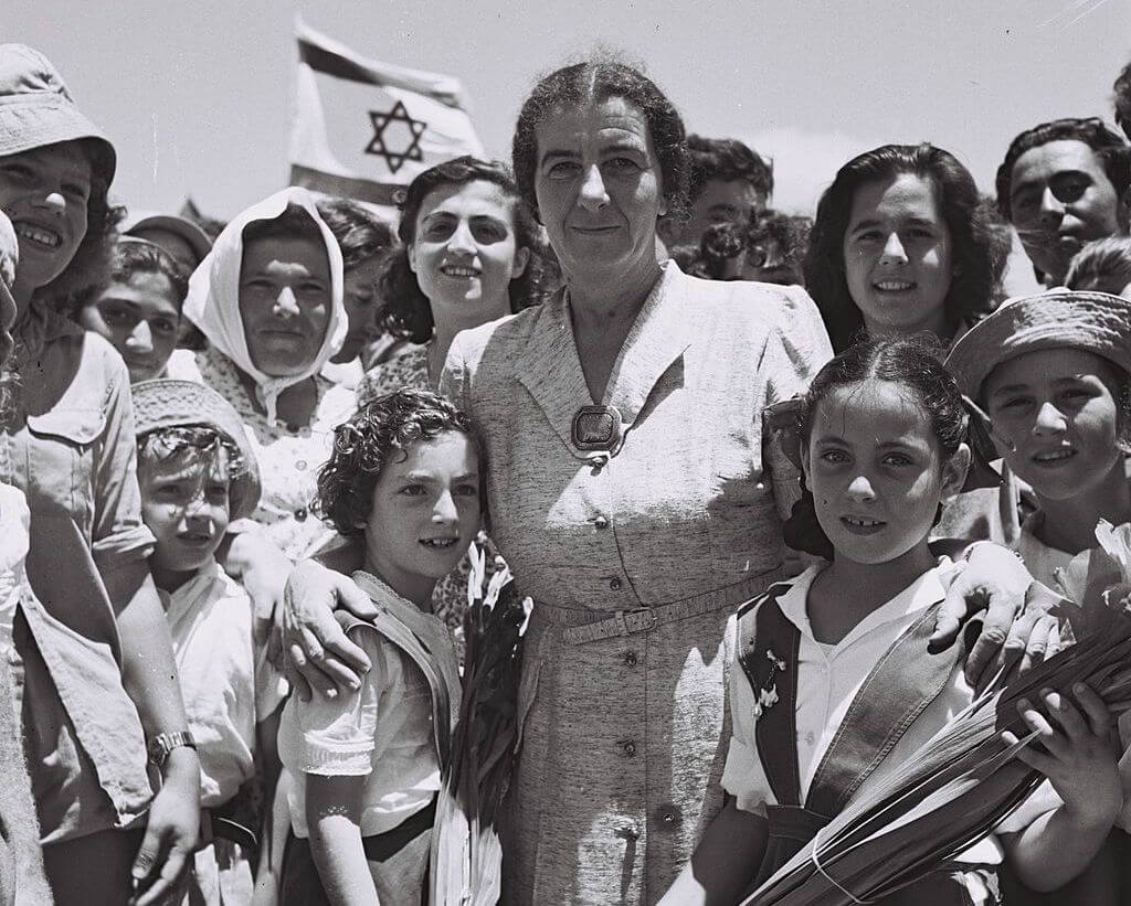 Golda Meir poses with a picture with the children of Kibbutz Shefaim, July 24, 1950 (Photo: Wikimedia)