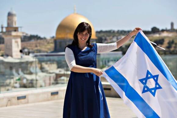 Tzipi Hotovely waving an Israeli flag with the Dome of the Rock in the background, in a 2014 promotion
