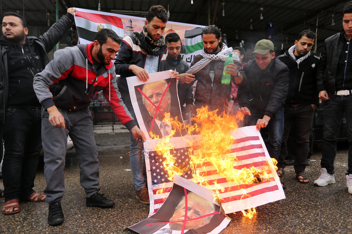 Palestinians burn posters depicting U.S. President Donald Trump and Israeli Prime Minister Benjamin Netanyahu during a protest against the U.S. intention to move its embassy to Jerusalem and to recognize the city of Jerusalem as the capital of Israel, in Rafah in the southern Gaza Strip December 6, 2017. (Photo: Ashraf Amra/APA Images)