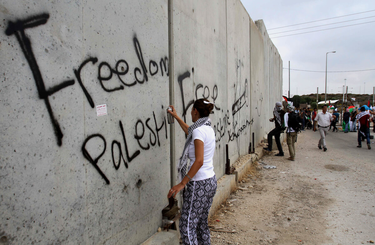 Protester sprays wall in Tulkarem