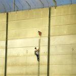 A Palestinian protester scaling the Gaza wall at the Karni crossing, July 20, 2018.