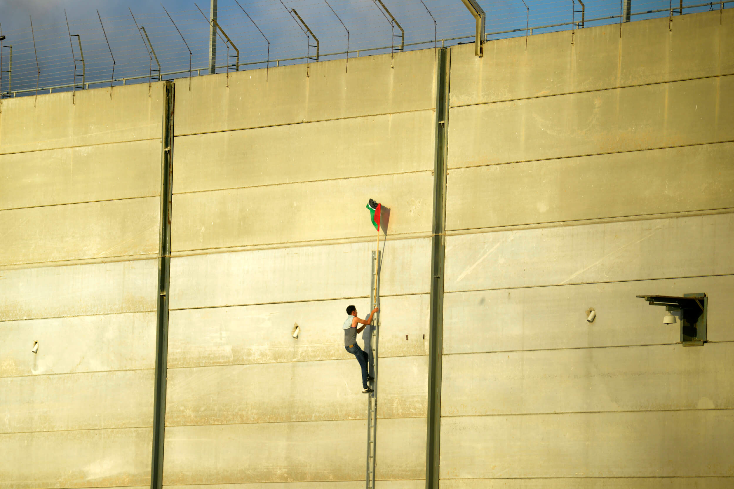 A Palestinian protester scaling the Gaza wall at the Karni crossing, July 20, 2018.