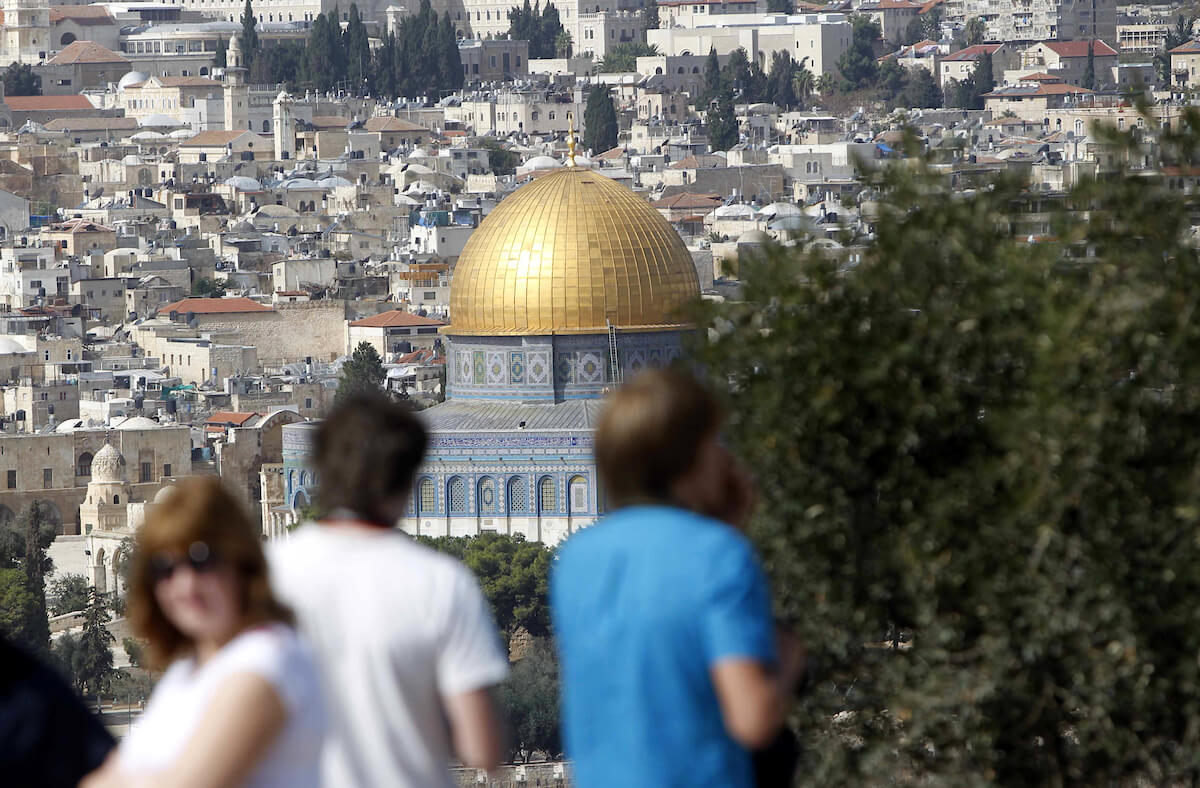 Tourists stand at the Mount of Olives, overlooking the Al-Aqsa mosque compound, in Jerusalem's Old City on November 04, 2014.