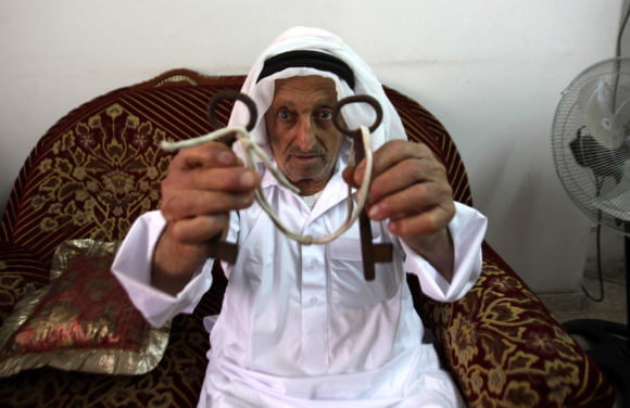 Palestinian refugee Abdulrahim Saad, 82, holds the keys of his former house in the city of Lod as he sits at his home in the West Bank refugee camp of Askar, near Nablus, May 13, 2015. Many Palestinians keep the keys of their former properties as a symbol for both, of what they had to leave behind and to where they once intend to return. (Photo: Nedal Eshtayah/APA Images)