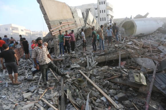 People inspect the remains of the the Said al-Mishal Foundation for Culture and Science in Gaza.