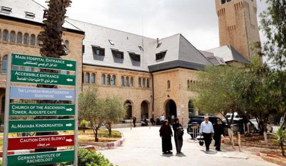 People walk outside of the Augusta Victoria hospital in East Jerusalem on Sunday. The US plans to cut $25 million in aid to six hospitals primarily serving Palestinians in Jerusalem.