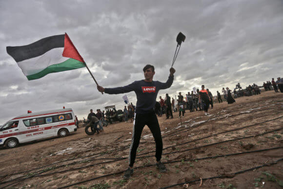 Aed Abu Amro winds a slingshot and waves a Palestinian flag, Friday, October 26, 2018.
