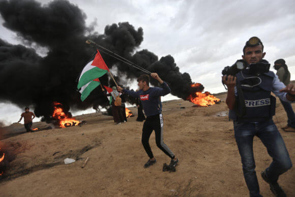 Aed Abu Amro waves a Palestinian flag at a protest in the Gaza Strip on Friday, October 26, 2018.